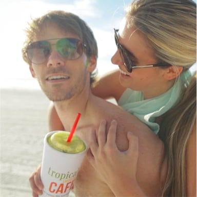 Couple on the beach enjoying a Tropical Smoothie Cafe smoothie