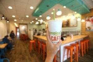 Interior of a Tropical Smoothie Cafe with someone holding up a smoothie cup