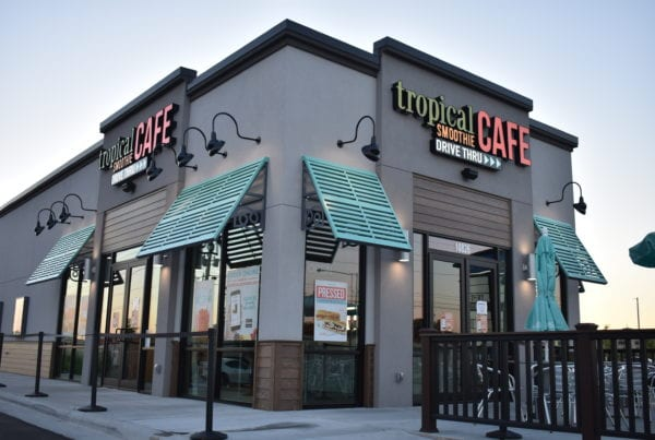 Tropical smoothie cafe location, gray building with blue awnings