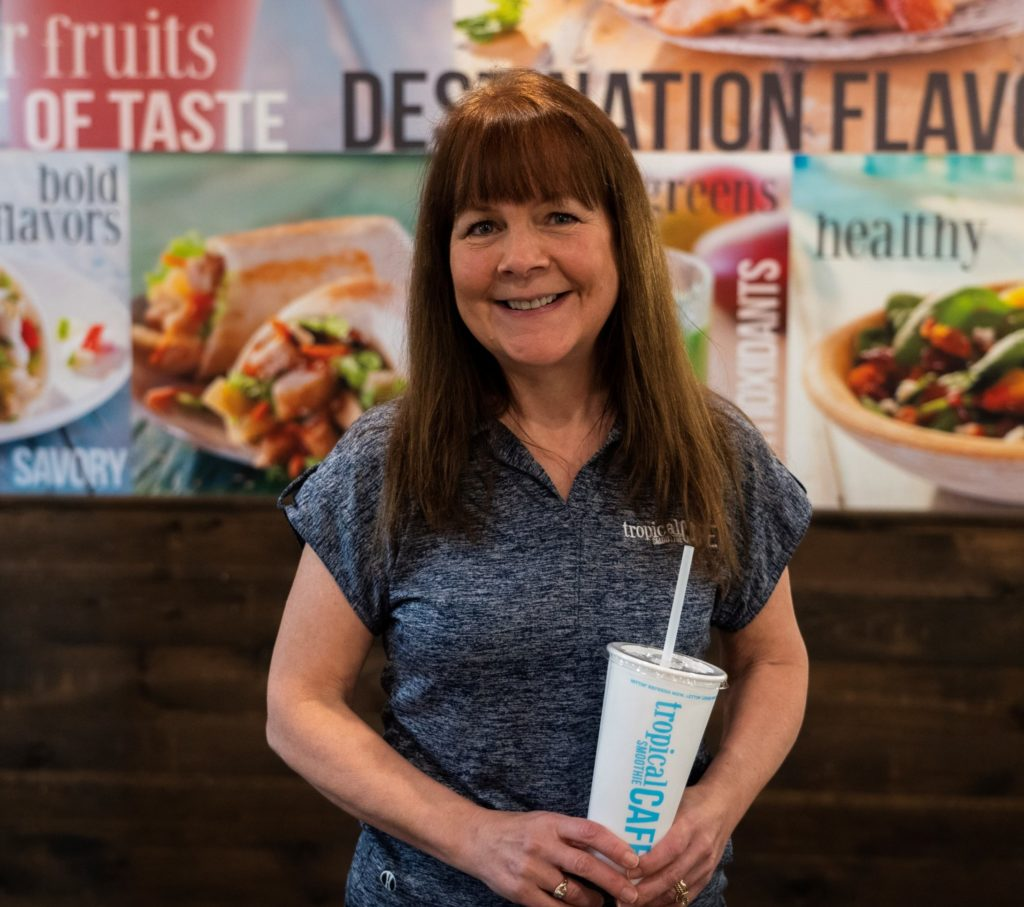 Tropical Smoothie Cafe franchise owner laura jankowski holing a smoothie cup and smiling